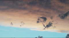 Panning shot of a sun light sky with darker coulds lingering in the foreground Stock Footage