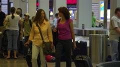 SALT LAKE CITY, UTAH - CIRCA 2012: Two women leave baggage claim at the airport Stock Footage