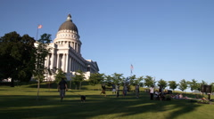 People lounge in the shadows of the Utah capitol building Stock Footage