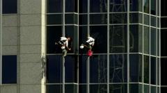 Two maintenance men washing windows in unison Stock Footage