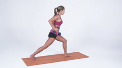Stock Video Footage of Young woman does arm exercises standing on a yoga mat in workout attire
