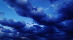 Dark clouds in a deep blue sky roll left across the sky. Stock Footage