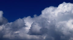 White cumulus clouds speeding furiously across an indigo sky. - stock footage