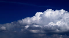 White cumulus clouds roll across an indigo sky Stock Footage