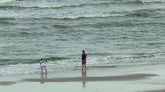 A young couple is walking along the surfs Stock Footage