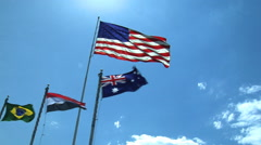 An American flag flies along with other countries' against a blue sky. Stock Footage