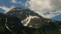 Time-lapse of a high mountain peak with snow patches and clouds. Stock Footage
