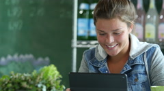 Young woman using an ipad/computer in a cafe - stock footage
