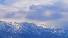 Panning time-lapse shot of snow-covered mountain peaks in Utah Stock Footage