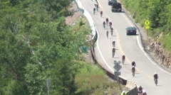 Cyclists Ride Toward Camera Hilly Rural Road in Triathlon Stock Footage