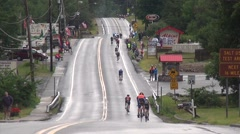 Cyclists Ride Away on Hilly Rural Road in Triathlon Stock Footage
