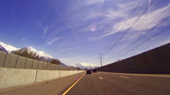 Sped-up dolly shot of vehicles on a highway in Utah with lens flare Stock Footage
