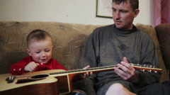 Young father teaches his young son to play guitar Stock Footage