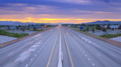 Time-lapse shot of traffic on a highway in Utah taken from an overpass at sunset - stock footage