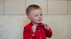 Little boy puts himself collar shirt Stock Footage
