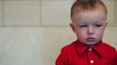 Sad little boy in a red shirt Stock Footage