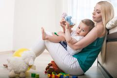 Cheerful young mom is embracing her little child Stock Photos