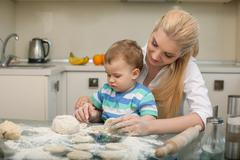 Pretty young housewife is cooking with her child - stock photo