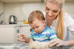 Cheerful young mom and her small son are baking - stock photo