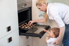 Pretty healthy family is cooking in the kitchen - stock photo