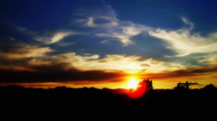 Vidid sunset over some distant mountains, and behind some silhouetted trees. Stock Footage