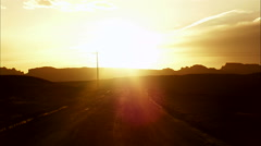 Looking down a road at the sun setting in the desert. - stock footage