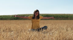 Stock Video Footage of Dark haired woman meditating in a wheat field