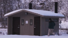 Man fruitlessly tries outhouse doors at a snowy road stop Stock Footage