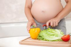 Young pregnant woman is making a salad in kitchen - stock photo