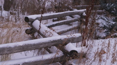 Rural stacked-wood fence in a snow-covered field Stock Footage