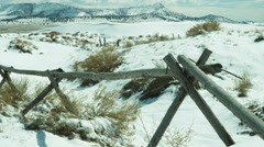 Pan of rural fence among snowy hills Stock Footage