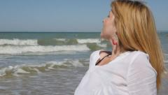 Beautiful blond woman enjoying and relaxing by the ocean slow motion 1080p Fu - stock footage