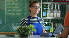 A young woman cashier taking payment from a customer Stock Footage