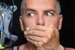 Man Covers Mouth After Smelling Shoe - stock photo