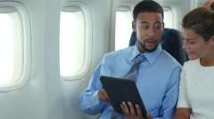 2 passengers sharing an ipad/tablet on a plane Stock Footage