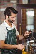 Barista steaming milk at the coffee machine Stock Photos