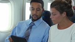 2 passengers on a plane sharing an electronic device Stock Footage
