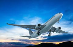 Commercial airplane flying at sunset Stock Photos