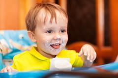 Happy child dirty with cream yoghurt Stock Photos