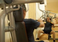 Mature man exercising on shoulder press machine Stock Photos