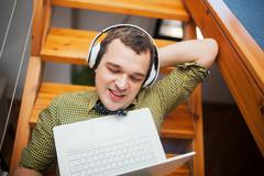 Man entertaining with laptop and music at home - stock photo