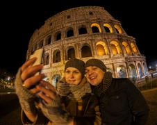 Happy couple making selfie by Coliseum at night Stock Photos