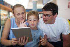 Parents and son with tablet PC at the airport Stock Photos
