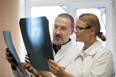 Professor and young doctor comparing x-rays Stock Photos