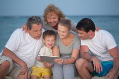 Happy big family with tablet PC on the beach Stock Photos
