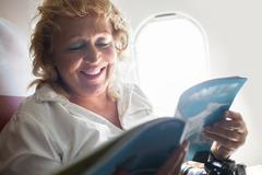 Mature Woman Reading Magazine on a Plane Stock Photos