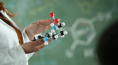 Chemistry teacher holding a molecular model, close up - stock footage