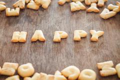 Happy alphabet biscuit on wooden table Stock Photos