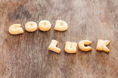 Good luck alphabet biscuit on wooden table Stock Photos