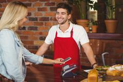 Pretty customer making a mobile payment - stock photo